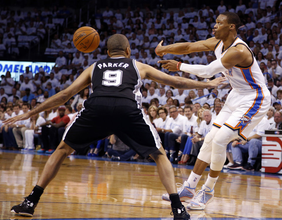 Photo - Oklahoma City's Russell Westbrook (0) passes the ball as San Antonio's Tony Parker (9) defends during Game 6 of the Western Conference Finals in the NBA playoffs between the Oklahoma City Thunder and the San Antonio Spurs at Chesapeake Energy Arena in Oklahoma City, Saturday, May 31, 2014. Photo by Bryan Terry, The Oklahoman
