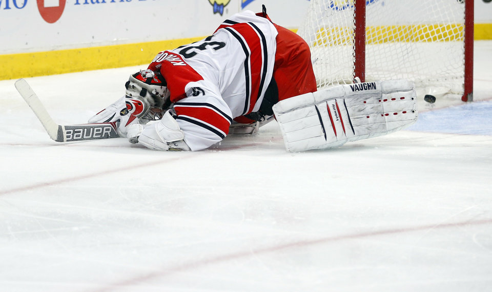 Photo - Carolina Hurricanes goalie Anton Khudobin reacts after giving up a goal against the Chicago Blackhawks during the second period of an NHL hockey game in Chicago, Friday, March 21, 2014. (AP Photo/Jeff Haynes)