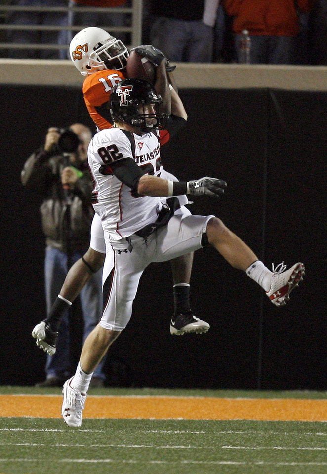 Photo - OSU's Perrish Cox (16) intercepts a pass intended for Texas Tech's Adam James (82) during the college football game between Oklahoma State University (OSU) and Texas Tech University at Boone Pickens Stadium in Stillwater, Okla. Saturday, Nov. 14, 2009. Photo by Sarah Phipps, The Oklahoman