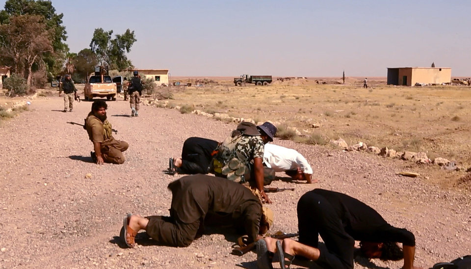 Photo - This undated image posted  Wednesday, Aug. 27, 2014 by the Raqqa Media Center of the Islamic State group, a Syrian opposition group, which has been verified and is consistent with other AP reporting, shows fighters from the Islamic State group that captured the Tabqa air base from the Syrian government on Sunday, praying inside the air base, in Raqqa, Syria.  A U.N. commission on Wednesday accused the extremist Islamic State organization of committing crimes against humanity with attacks on civilians, as pictures emerged of the extremists' bloody takeover of a Syrian military air base that added to the international organization's claims.  (AP Photo/ Raqqa Media Center of the Islamic State group)