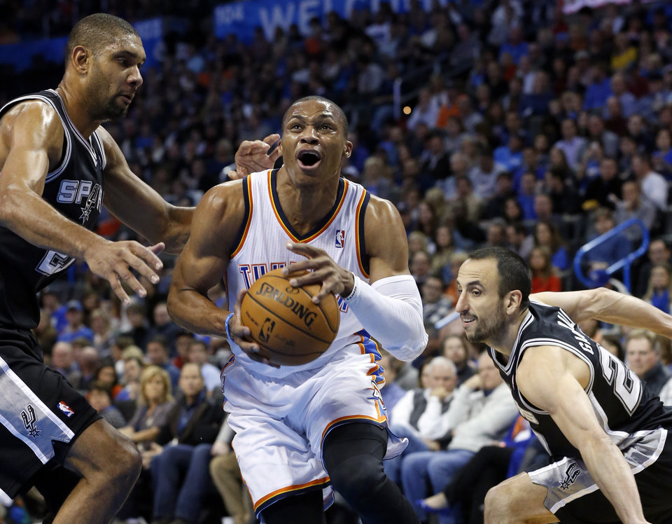 Oklahoma City Thunder guard Russell Westbrook (0) drives between San Antonio Spurs forward Tim Duncan (21) and guard Manu Ginobili (20) in the first quarter of an NBA basketball game in Oklahoma City, Wednesday, Nov. 27, 2013. (AP Photo/Sue Ogrocki)