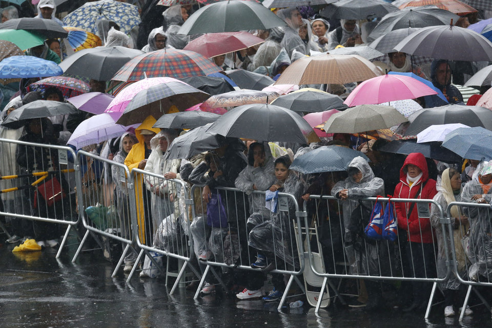 Photo - Pilgrims wait under the rain for the arrival of Pope Francis outside the Aparecida basilica in Aparecida, Brazil, Wednesday July 24, 2013. Pope Francis, the first pontiff from the Americas, will fly over farmland and sugar cane fields to visit the mammoth basilica that holds the statue of this particular Brazilian Mary.(AP Photo/Victor R. Caivano)