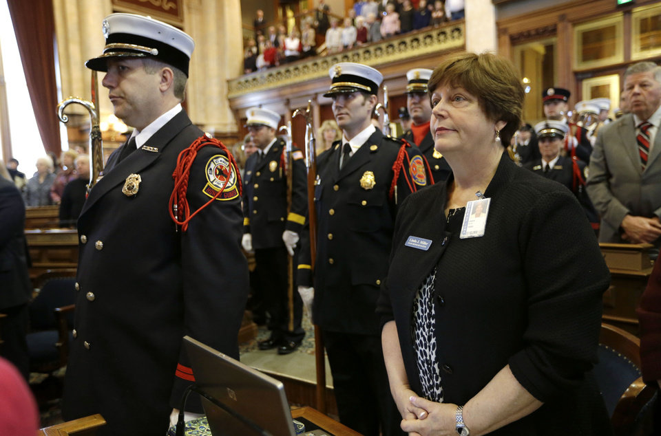 Photo - Rep. Linda Miller, R-Bettendorf, right, looks on during the opening prayer during the first day of the Iowa Legislature, Monday, Jan. 14, 2013, at the Statehouse in Des Moines, Iowa. (AP Photo/Charlie Neibergall)