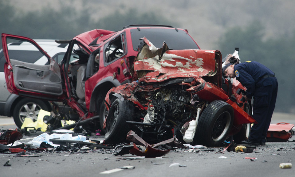 Photo - CORRECTS YEAR TO 2014 INSTEAD OF 2013 - Officials investigate the scene of a multiple vehicle accident where six people were killed on the westbound Pomona Freeway in Diamond Bar, Calif., on Sunday morning, Feb. 9, 2014. Authorities say four members of a family have been killed in the wrong-way freeway crash that also took the life of two others, including the sister of a woman arrested on suspicion of drunken driving. (AP Photo/San Gabriel Valley Tribune,Watchara Phomicinda)