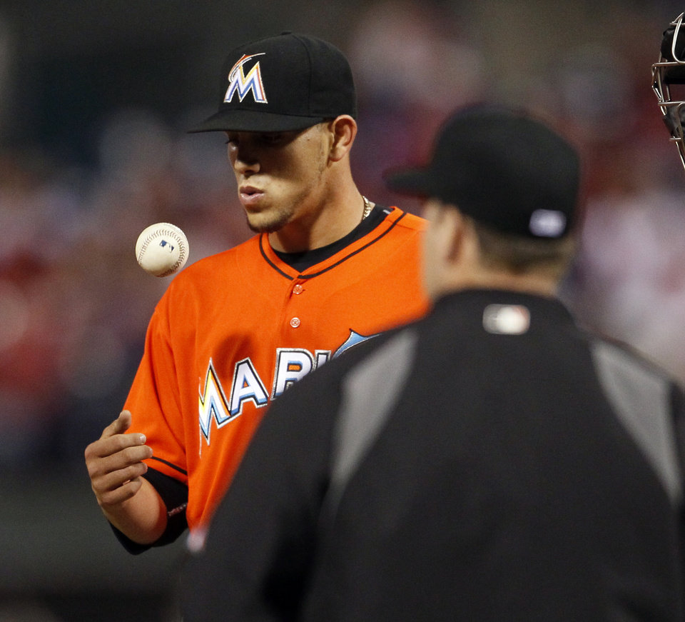 Photo - Miami Marlins' Jose Fernandez tosses the ball as he waits for manager Ryne Sandberg, right, to take him out during the fifth inning of a baseball game against the Philadelphia Phillies, Friday, April 11, 2014, in Philadelphia. (AP Photo/Tom Mihalek)