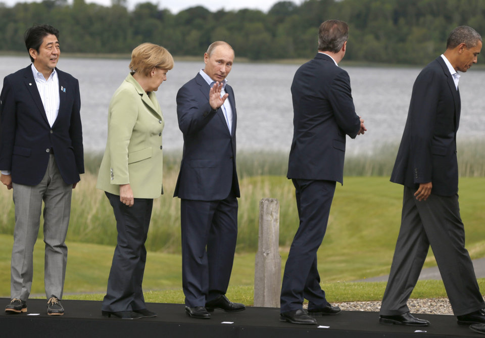 Photo - G-8 leaders from left, Japan's Prime Minister Shinzo Abe, German Chancellor Angela Merkel, Russian President Vladimir Putin, British Prime Minister David Cameron and US President Barack Obama leave the podium after a group photo opportunity during the G-8 summit at the Lough Erne golf resort in Enniskillen, Northern Ireland, on Tuesday, June 18, 2013. The final day of the G-8 summit of wealthy nations is ending with discussions on globe-trotting corporate tax dodgers, a lunch with leaders from Africa, and suspense over whether Russia and Western leaders can avoid diplomatic fireworks over their deadlock on Syria's civil war. (AP Photo/Lefteris Pitarakis)