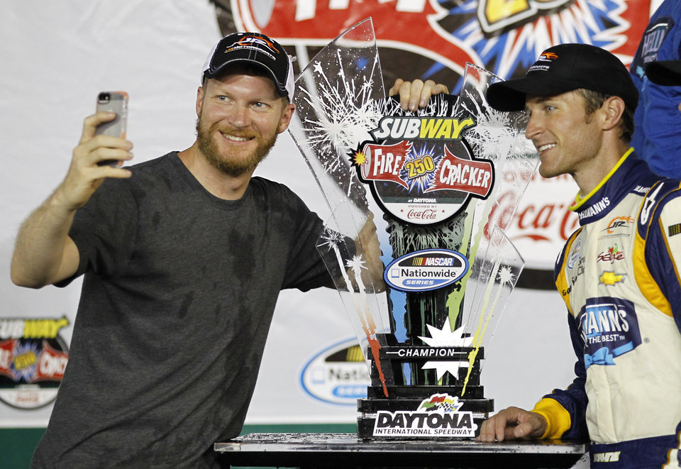 Photo - Dale Earnhardt Jr., left, takes a  photo with NASCAR Nationwide series auto race winner Kasey Kahne at Daytona International Speedway in Daytona Beach, Fla., Friday, July 4, 2014. (AP Photo/Terry Renna)