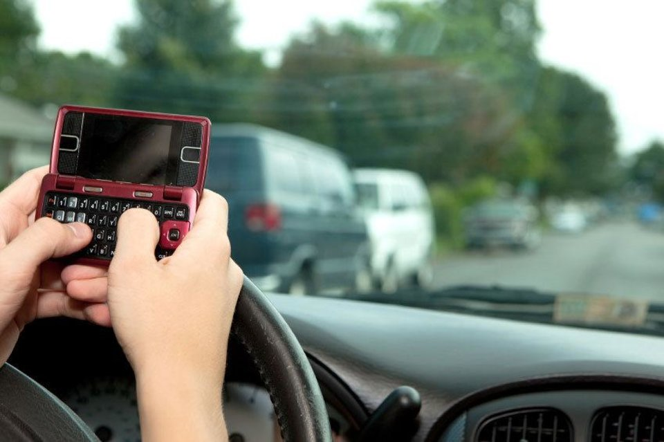 Photo - A driver composes a text message  while driving.   - AP photo illustration