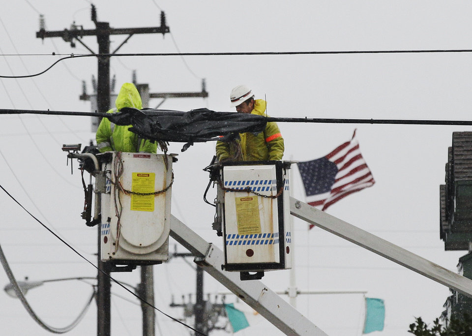 Linemen work during blowing wind and rain to restore power to the area ahead of an incoming Nor'easter storm, Wednesday, Nov. 7, 2012, in Surf City, on Long Beach Island N.J.  A nor'easter smacked the storm-ravaged Jersey shore on Wednesday, a week and half after Superstorm Sandy wrecked many of its beaches, dunes and boardwalks, and left low-lying communities newly vulnerable to flooding, wind damage and power outages. Public works crews up and down the shore were using bulldozers, front-end loaders and earth movers to push tons of sand back onto what was left of the beaches.  (AP Photo/Mel Evans) ORG XMIT: NJME101
