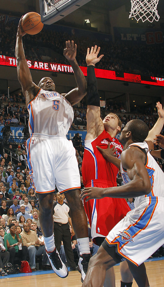 Photo - Oklahoma City Thunder center Kendrick Perkins (5) puts up a shot over Los Angeles Clippers power forward Blake Griffin (32) during the NBA basketball game between the Oklahoma City Thunder and the Los Angeles Clippers at Chesapeake Energy Arena on Wednesday, March 21, 2012 in Oklahoma City, Okla.  Photo by Chris Landsberger, The Oklahoman
