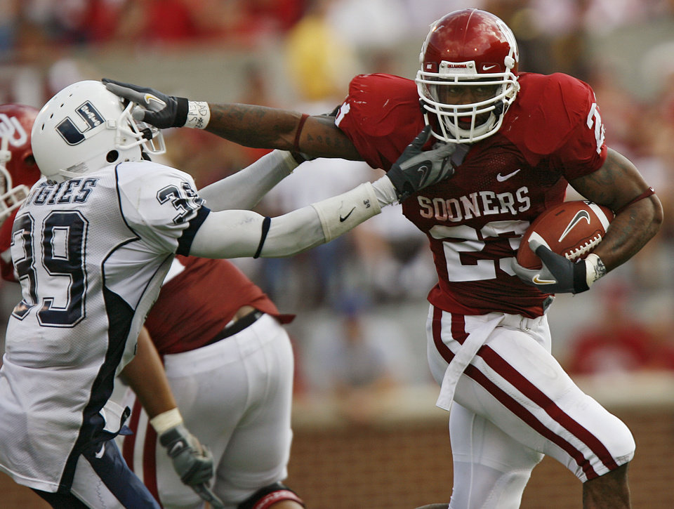 Photo - Oklahoma's Allen Patrick (23) stiff arms Utah State's Caleb Taylor (39)  in the second half during the University of Oklahoma Sooners (OU) college football game against the Utah State University Aggies (USU) at the Gaylord Family -- Oklahoma Memorial Stadium, on Saturday, Sept. 15, 2007, in Norman, Okla.     By JAMES PLUMLEE, The Oklahoman  ORG XMIT: KOD