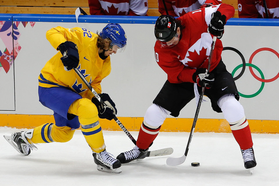 Photo - Carl Hagelin of Sweden (62) and Patrick Sharp of Canada (10) battle for control of the puck during the second period of the men's gold medal ice hockey game at the 2014 Winter Olympics, Sunday, Feb. 23, 2014, in Sochi, Russia. (AP Photo/Petr David Josek)