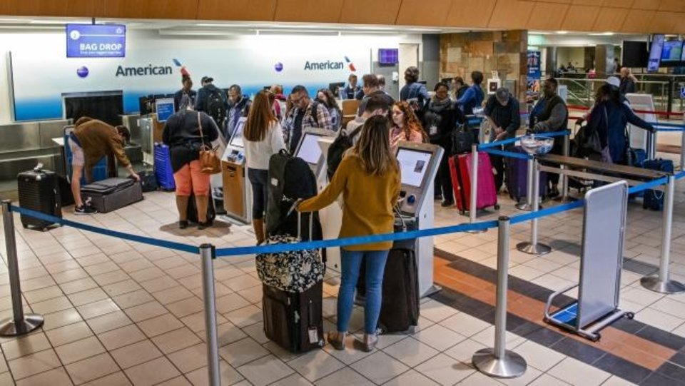 Photo -  Travelers stand in line Friday to get tickets and check their bags at Will Rogers World Airport.  [Chris Landsberger/The Oklahoman]