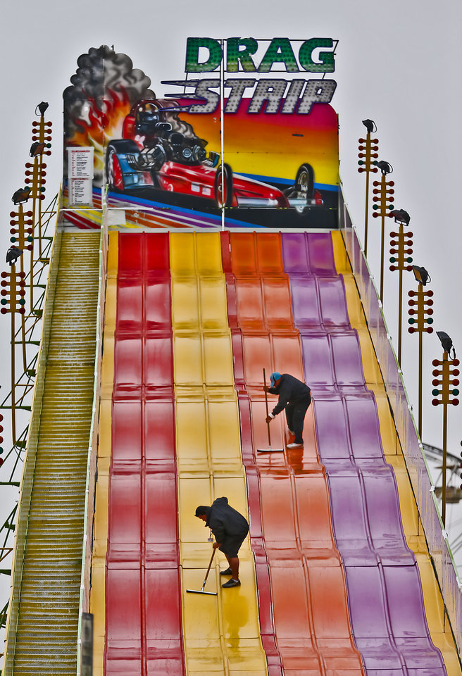 Photo - Workers clear water off of a midway ride at the Oklahoma State Fair at State Fair Park on Friday, Sept. 14, 2012, in Oklahoma City, Oklahoma.  Photo by Chris Landsberger, The Oklahoman