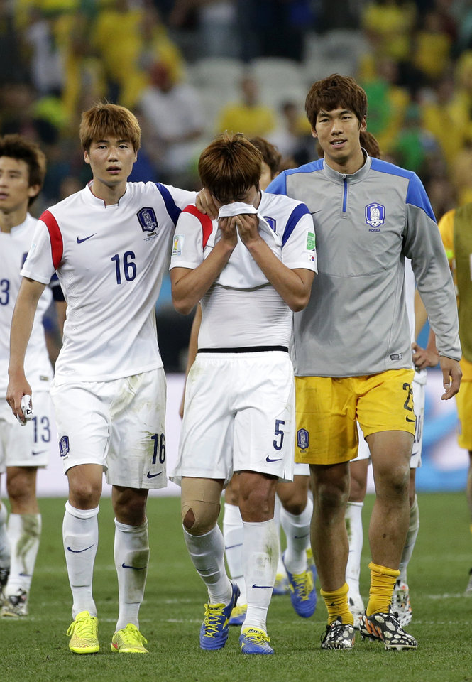 South Korea\'s Kim Young-gwon, center, is comforted by his teammates Ki Sung-yueng, left, and goalkeeper Lee Bum-young, right, after the group H World Cup soccer match between South Korea and Belgium at the Itaquerao Stadium in Sao Paulo, Brazil, Thursday, June 26, 2014. Belgium beat South Korea 1-0 to top Group H of the World Cup. South Korea was eliminated. (AP Photo/Felipe Dana)