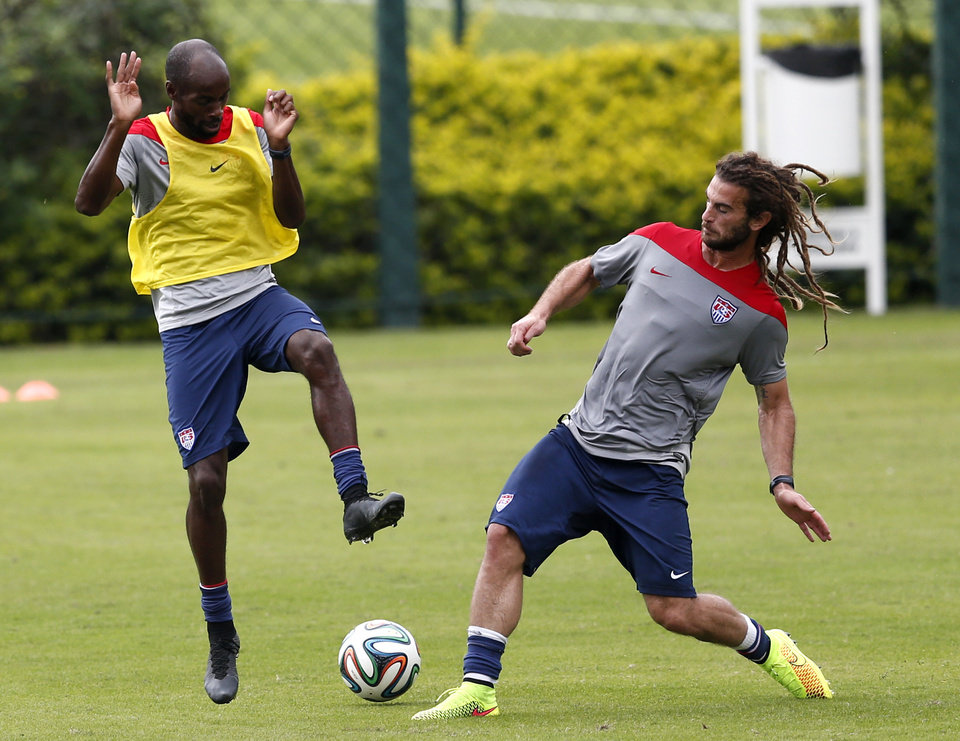 Photo - United States' DaMarcus Beasley, left, and Kyle Beckerman compete for the ball during a training session at the Sao Paulo FC training center in Sao Paulo, Brazil, Wednesday, June 11, 2014. The U.S. will play in group G of the 2014 soccer World Cup. (AP Photo/Julio Cortez)