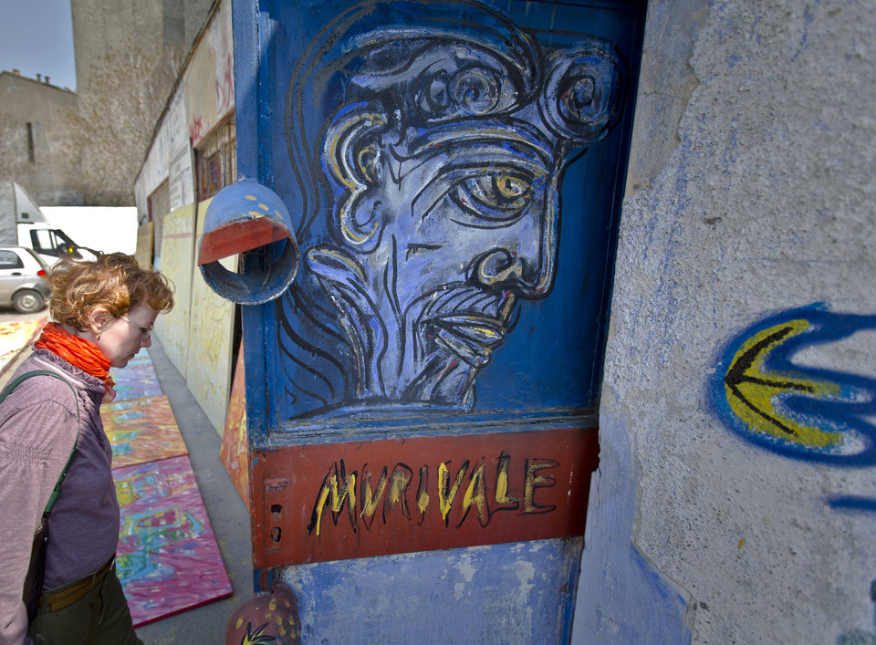 Photo - In this photo taken on April 4, 2013, a woman enters a storage room containing works by Romanian artist Vasile Muresan, known as Murivale,  in a parking lot,  in Bucharest, Romania. The white-bearded painter can often be seen sitting on his colorful canvasses which he displays in the street followed by the street dogs which are his companions and also inspire his work. The 56-year-old, whose home city is Bistrita_the Transylvanian town associated with the legendary Count Dracula_ has been painting with passion since he was a teen, producing vivid works of Monaco, the streets of Paris, the hurly burly of the Romanian capital and huge colorful more abstract canvasses. (AP Photo/Vadim Ghirda)