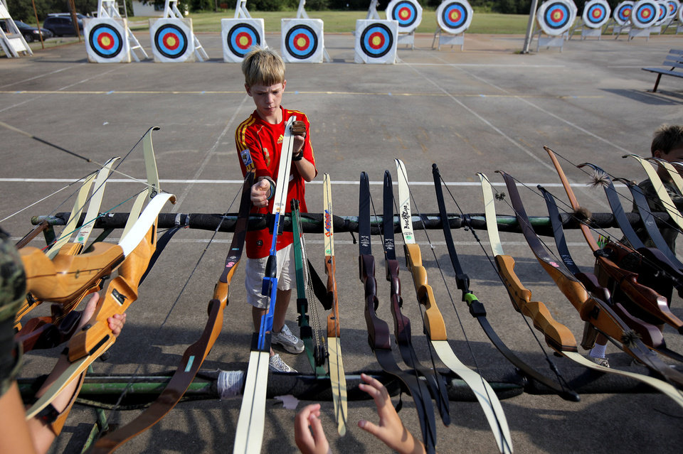 Photo - Matthew White, 12, of Norman picks up his bow during a Junior Olympic Archery Development Club shoot put on by the Trosper Archery Club on Saturday, August 24, 2013, at Trosper Park in Oklahoma City. White has been shooting for 3 years but was attending this shoot for the first time along with over 60 participants, from beginners to intermediates, that took part in the shoot which takes place every Saturday. For $5 each person is supplied with equipment and instruction starting at 9am for beginners and 10am for intermediate shooters. Photo by Bryan Terry, The Oklahoman