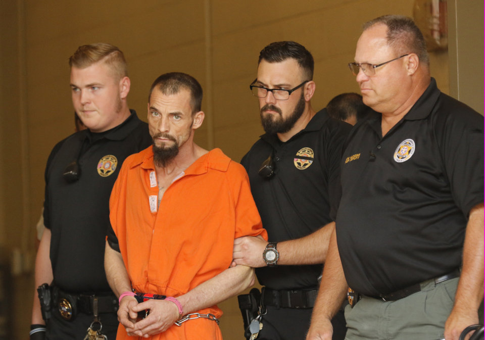 Photo -  Nathan LeForce is taken into the Logan County Courthouse for his arraignment in Guthrie on Thursday. LeForce is accused of killing Logan County Deputy David Wade. [Photo By Steve Gooch, The Oklahoman]