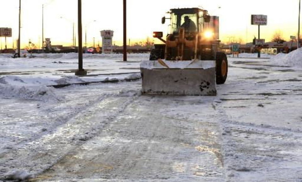 Photo - A loader works at sunrise to clear snow and ice from a shopping mall parking lot at I-240 and S. Pennsylvania in Oklahoma City Thursday, Feb. 10, 2011. Photo by Paul B. Southerland
