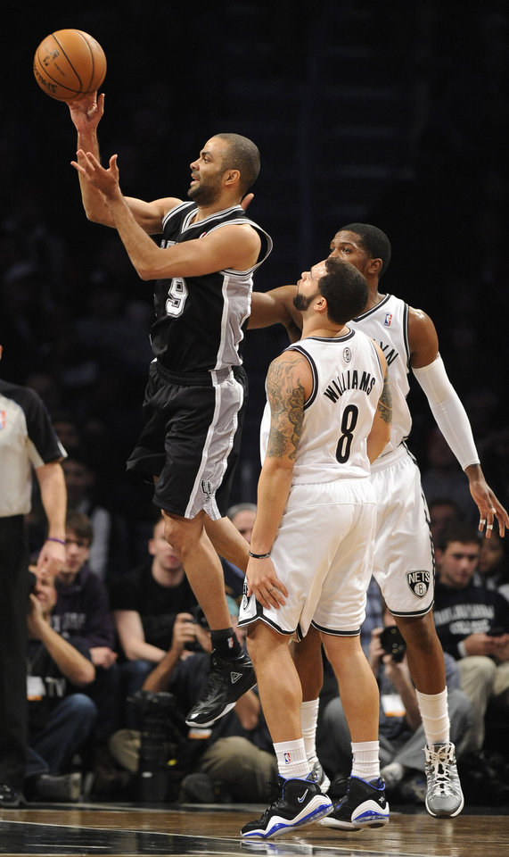 San Antonio Spurs\' Tony Parker (9) shoots past Brooklyn Nets\' Deron Williams (8) and Joe Johnson in the first half of an NBA basketball game, Sunday, Feb. 10, 2013, at Barclays Center in New York. The Spurs won 111-86. (AP Photo/Kathy Kmonicek)