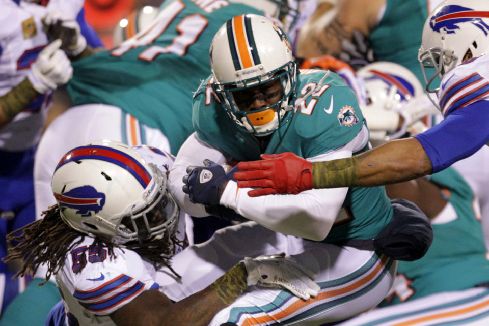 Buffalo Bills middle linebacker Kelvin Sheppard (55) tackles Miami Dolphins' Reggie Bush (22) during the first half of an NFL football game on Thursday, Nov. 15, 2012, in Orchard Park, N.Y. (AP Photo/Bill Wippert)