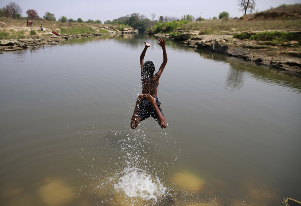 Photo - In this April 15, 2014 photo, a boy baths in the Kelo River, where little black coal nuggets now populate the riverbed, in Gare village, near the industrial city of Raigarh, Chhattisgarh state, India. Villagers say the coal mine dumps waste water into the river at night. (AP Photo/Rafiq Maqbool)