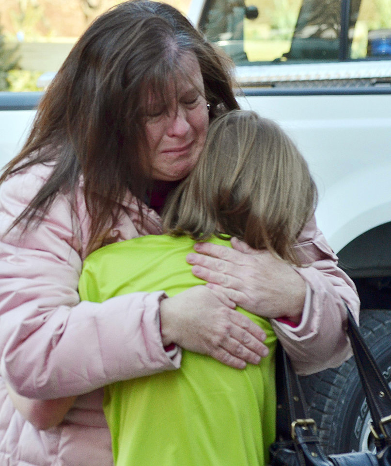 Photo - A mother hugs her daughter following a shooting at the Sandy Hook Elementary School in Newtown, Conn., about 60 miles (96 kilometers) northeast of New York City, Friday, Dec. 14, 2012. An official with knowledge of Friday's shooting said 27 people were dead, including 18 children. It was the worst school shooting in the country's history. (AP Photo/The New Haven Register, Melanie Stengel)   ORG XMIT: CTNHR103