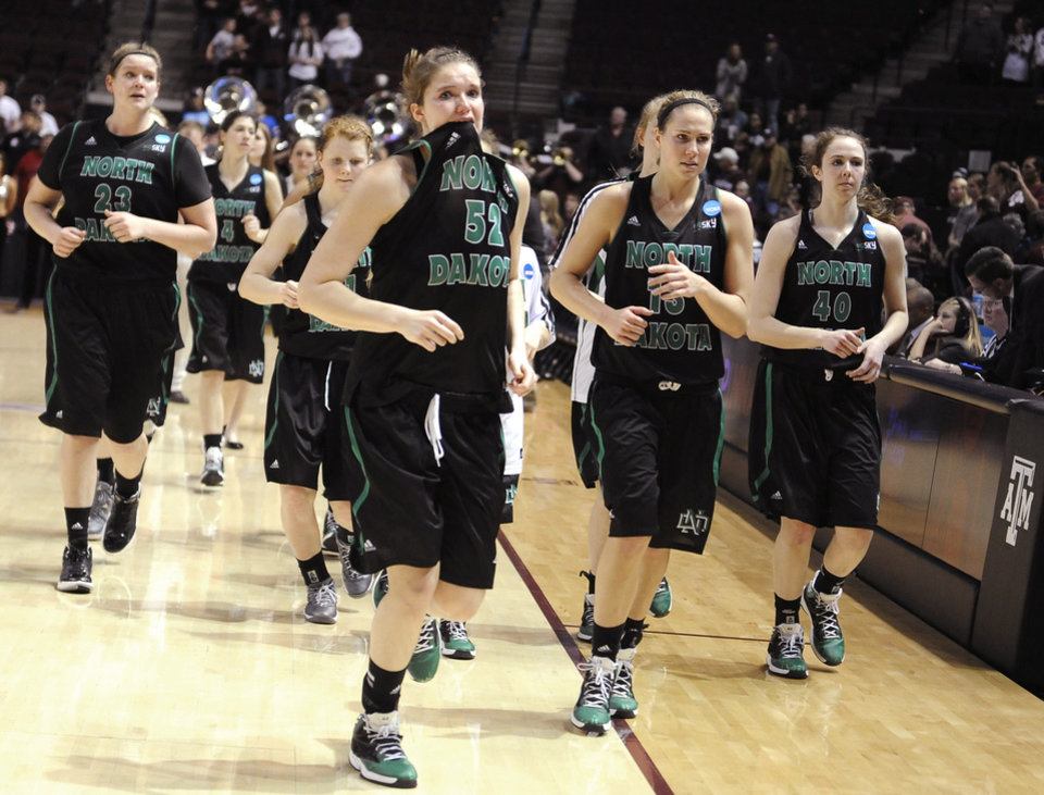 Photo - North Dakota's Allyssa Wall (52) and her teammates leave the floor after losing 70-55 to Texas A&M in a first-round NCAA women's basketball game Sunday, March 23, 2014, in College Station, Texas. A&M will face James Madison in the second round Tuesday night. (AP Photo/Pat Sullivan)