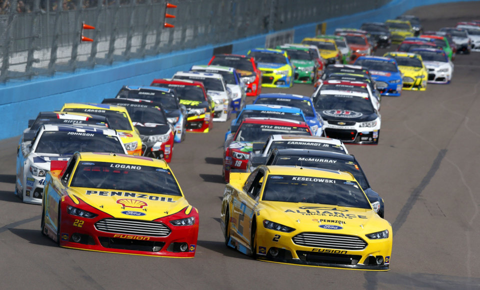 Photo - Joey Logano (22) and Brad Keselowski (2) lead into the first turn at the start of the NASCAR Sprint Cup Series auto race Sunday, March 2, 2014, in Avondale, Ariz. (AP Photo/Ross D. Franklin)