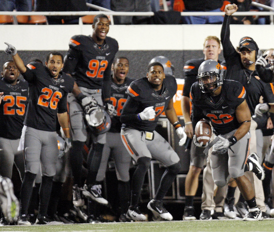 Photo - The OSU sideline reacts as Oklahoma State's James Thomas (22) returns an intercepted tipped pass during a college football game between the Oklahoma State University Cowboys (OSU) and the Kansas State University Wildcats (KSU) at Boone Pickens Stadium in Stillwater, Okla., Saturday, Nov. 5, 2011.  Photo by Nate Billings, The Oklahoman