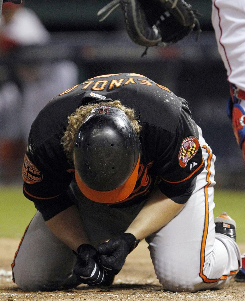Photo -   Baltimore Orioles' Mark Reynolds checks his hand after being hit by a pitch from Texas Rangers starter Yu Darvish during the second inning of an American League wild-card playoff baseball game Friday, Oct. 5, 2012, in Arlington, Texas. (AP Photo/LM Otero)
