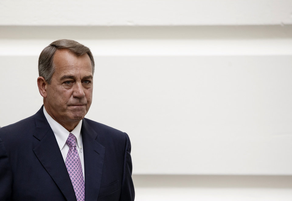 Photo - House Speaker John Boehner of Ohio walks to a Republican strategy session on Capitol Hill in Washington, Friday, Oct. 4, 2013. Boehner is struggling between Democrats that control the Senate and GOP conservatives in his caucus who insist any funding legislation must also kill or delay the nation's new health care law. Added pressure came from President Barack Obama who pointedly blamed Boehner on Thursday for keeping federal agencies closed. (AP Photo/J. Scott Applewhite)