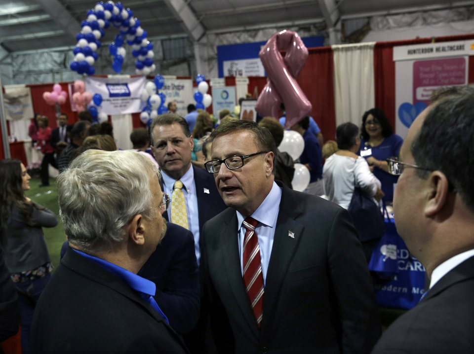Photo - Republican candidate for Senate Steve Lonegan, center right, striped tie, greets people in Flemington, N.J., Tuesday, Oct. 15, 2013, as he campaigns for Senate at a trade show. Lonegan is running against Democratic Newark Mayor Cory Booker in Wednesday's election. Cory Booker's path to Wednesday's U.S. Senate election has been bumpier than anticipated. Even Republicans had expected Booker, a Democrat in a Democratic-leaning state, to cruise to victory over little-known Steve Lonegan. But the charismatic Newark mayor has faced sustained Republican criticism that has exposed vulnerabilities that could hamper him should he seek higher office someday. (AP Photo/Mel Evans)