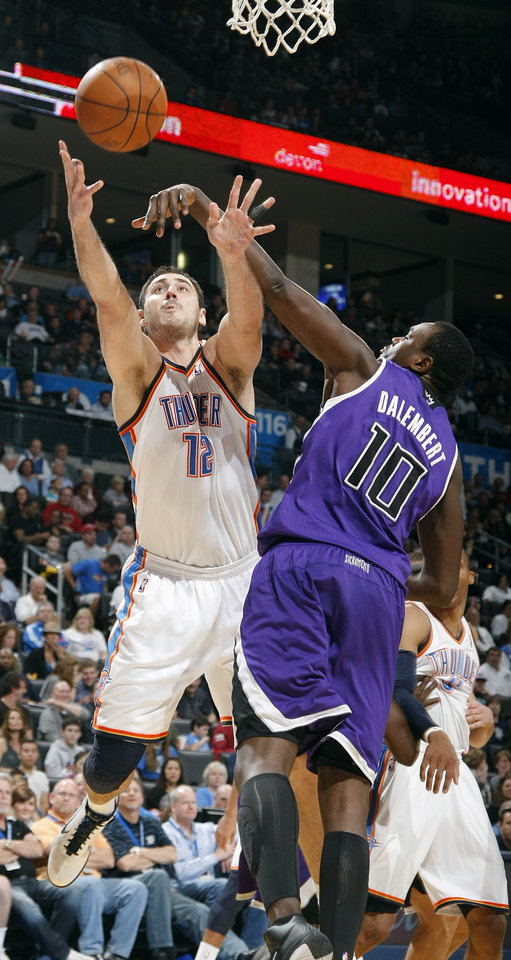 Photo - The Thunder's Nenad Krstic (12) lays up a shot past the Kings' Samuel Dalembert (10) during the NBA basketball game between the Oklahoma City Thunder and The Sacramento Kings on Tuesday, Feb. 15, 2011, Oklahoma City Okla.  Photo by Chris Landsberger, The Oklahoman