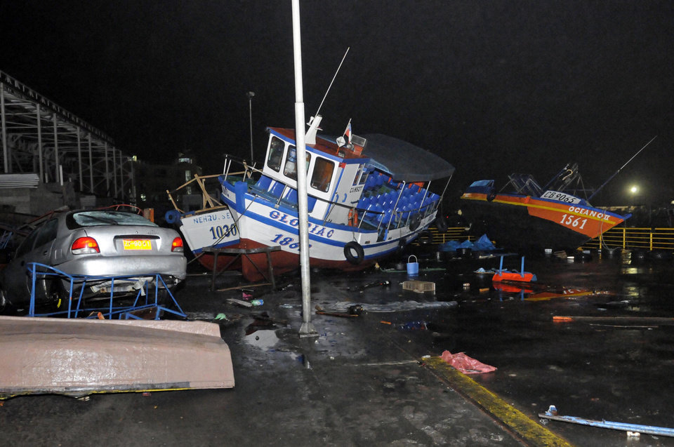 Photo - Fishing boats washed ashore by a small tsunami, sit in Caleta Riquelme, adjacent to the port, in the northern town of Iquique, Chile, after magnitude 8.2 earthqauke struck the northen coast of Chile, Wednesday, April 2, 2014. Authorities lifted tsunami warnings for Chile's long coastline early Wednesday. Six people were crushed to death or suffered fatal heart attacks, a remarkably low toll for such a powerful shift in the Earth's crust. (AP Photo/Cristian Viveros) NO PUBLICAR EN CHILE