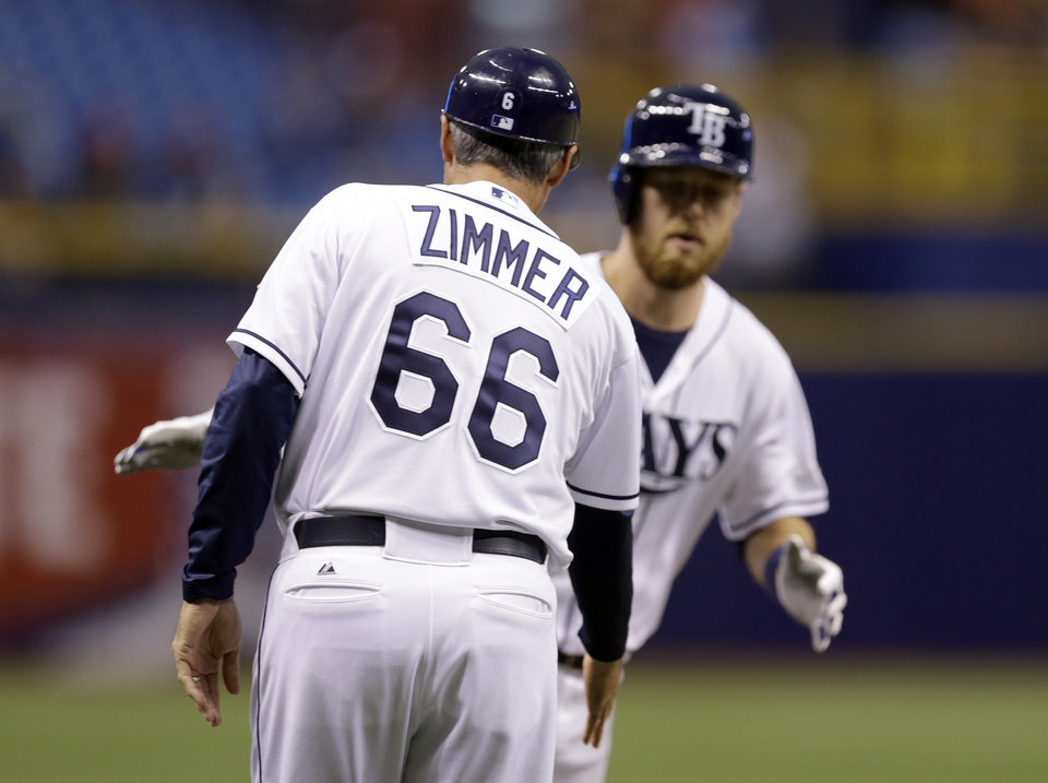 Photo - Tampa Bay Rays third base coach Tom Foley, wearing a jersey in honor of senior baseball advisor Don Zimmer, reaches out to shake hands with Ben Zobrist after Zobrist hit a two-run home run off Miami Marlins starting pitcher Tom Koehler during the first inning of an interleague baseball game Wednesday, June 4, 2014, in St. Petersburg, Fla. Foley had been wearing the jersey for a few weeks. (AP Photo/Chris O'Meara)
