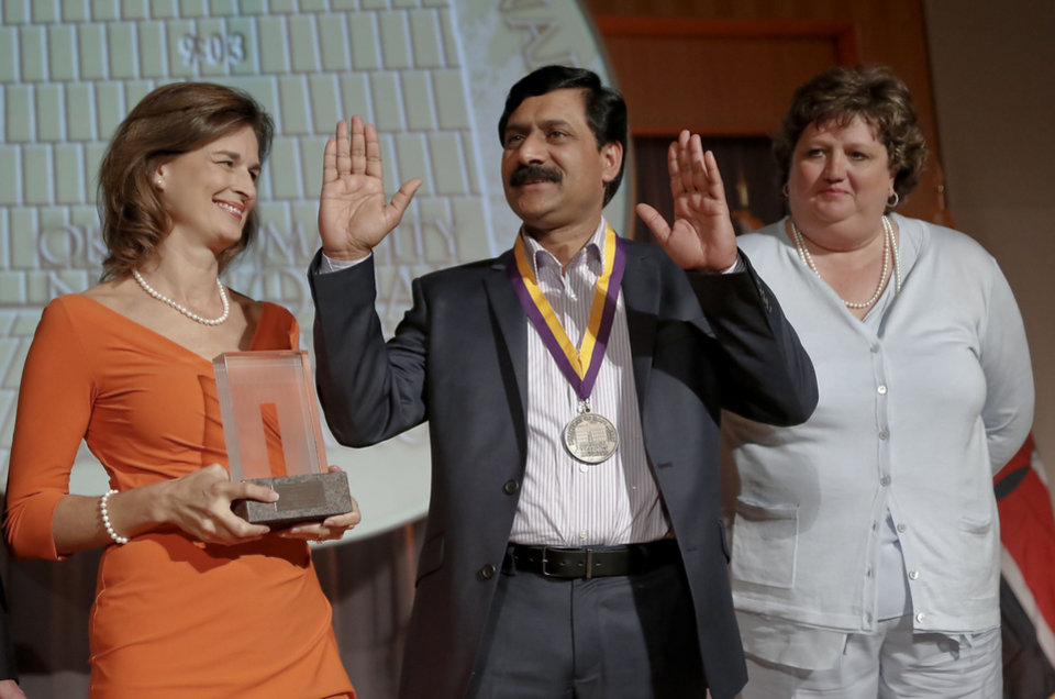 Photo - Ann-Clore Duncan, left, and Kari Watkins look on as Ziauddin Yousafzai acknowledges the crowd during the Reflections of Hope Award ceremony on Monday, May 13, 2013 in Oklahoma City, Okla. where Malala Yousafzai and her father Ziauddin were honored with the award for Malala's stand against the Taliban to have the right to an educated.  Photo by Chris Landsberger, The Oklahoman