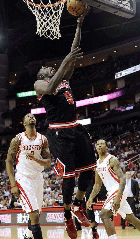 Photo -   Chicago Bulls' Luol Deng (9) shoots in front of Houston Rockets' Marcus Morris (2) and Greg Smith (4) in the first half of an NBA basketball game, Wednesday, Nov. 21, 2012, in Houston. (AP Photo/Pat Sullivan)