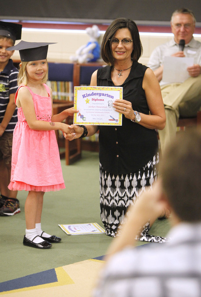 Photo - Kindergartner Jordyn Howsmon has her photo taken by a parent as she receives a diploma from her teacher, Debbie Crouch, during a kindergarten graduation ceremony at Centennial Elementary School in Edmond.  By Paul Hellstern, The Oklahoman  PAUL HELLSTERN - Oklahoman