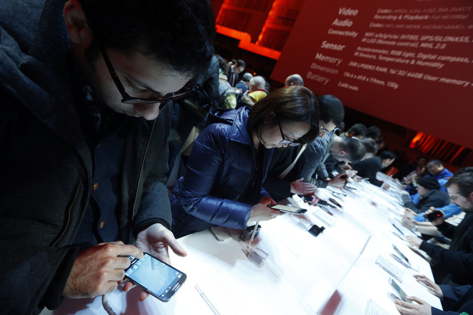 Photo - Attendees try out the new Samsung Galaxy S 4 during the Samsung Unpacked event at Radio City Music Hall, Thursday, March 14, 2013 in New York.  (AP Photo/Jason DeCrow)