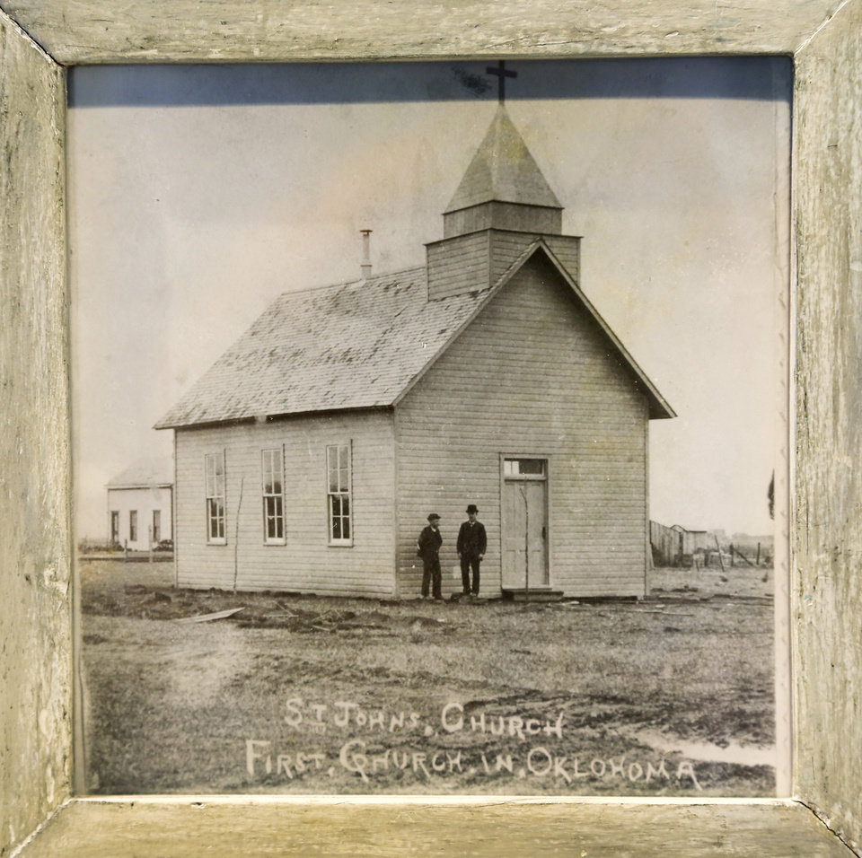 Photo -  The original structure that housed St. John the Baptist Catholic Church in Edmond is shown in this framed photograph on display at the church, 900 S Littler. The church building was constructed in 1889 in what was then Oklahoma Territory. Photo by Jim Beckel, The Oklahoman   Jim Beckel