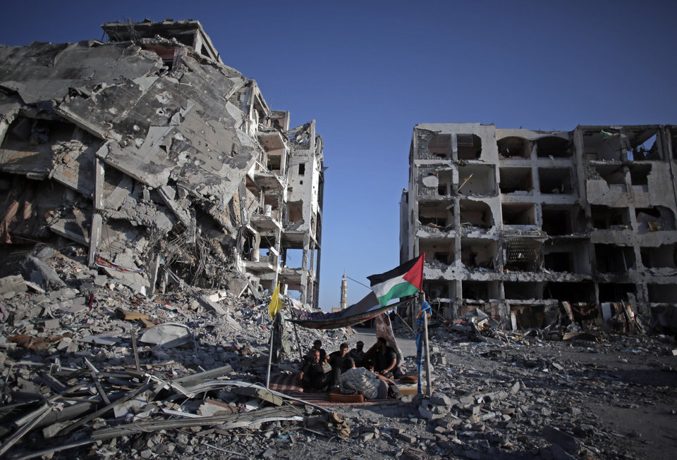 Photo - Palestinian Ziad Rizk, 38, sits with others in a shelter made of a blanket stretched over four boles next to one of the destroyed Nada Towers, where he lost his apartment and clothes shop, in the town of Beit Lahiya, northern Gaza Strip, Monday, Aug. 11, 2014. (AP Photo/Khalil Hamra)