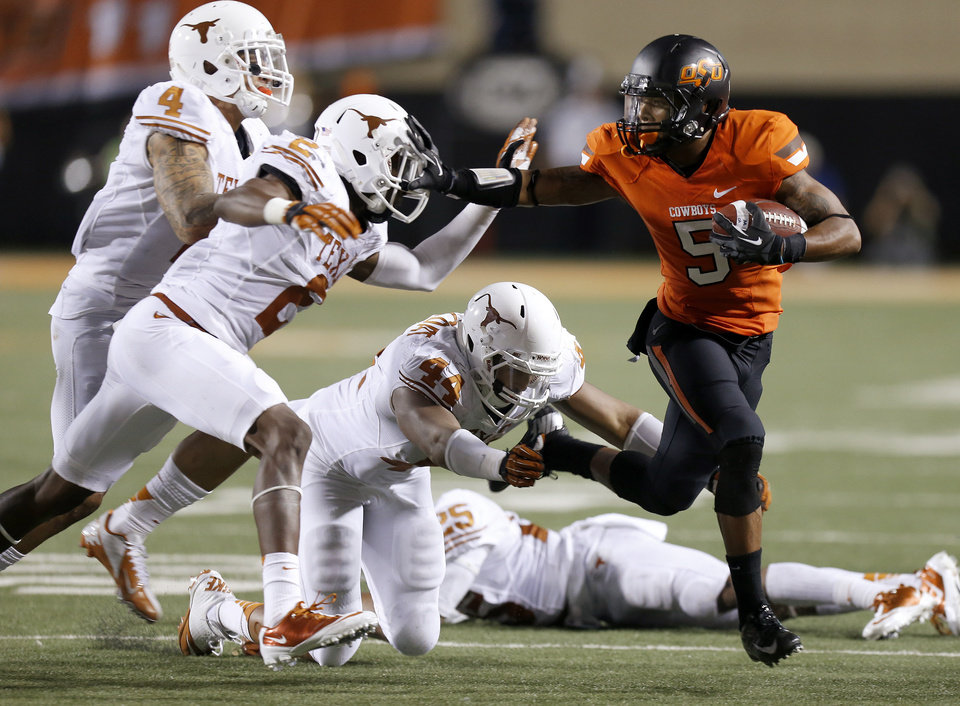 Photo - Oklahoma State's Josh Stewart (5) tries to get away from Texas' Kenny Vaccaro (4), Mykkele Thompson (2), and Jackson Jeffcoat (44)  during a college football game between Oklahoma State University (OSU) and the University of Texas (UT) at Boone Pickens Stadium in Stillwater, Okla., Saturday, Sept. 29, 2012. Oklahoma State lost 41-36. Oklahoma State lost 41-36. Photo by Bryan Terry, The Oklahoman
