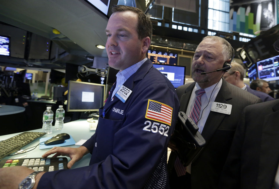Photo - Specialist Charles Boedinghaus, left, and trader Robert Moran, work at a post on the floor of the New York Stock Exchange, during the IPO of Parsley Energy, Friday, May 23, 2014. Founded in 2008, Parsley Energy is an independent oil and natural gas company with operations in the Permian Basin.  (AP Photo/Richard Drew)