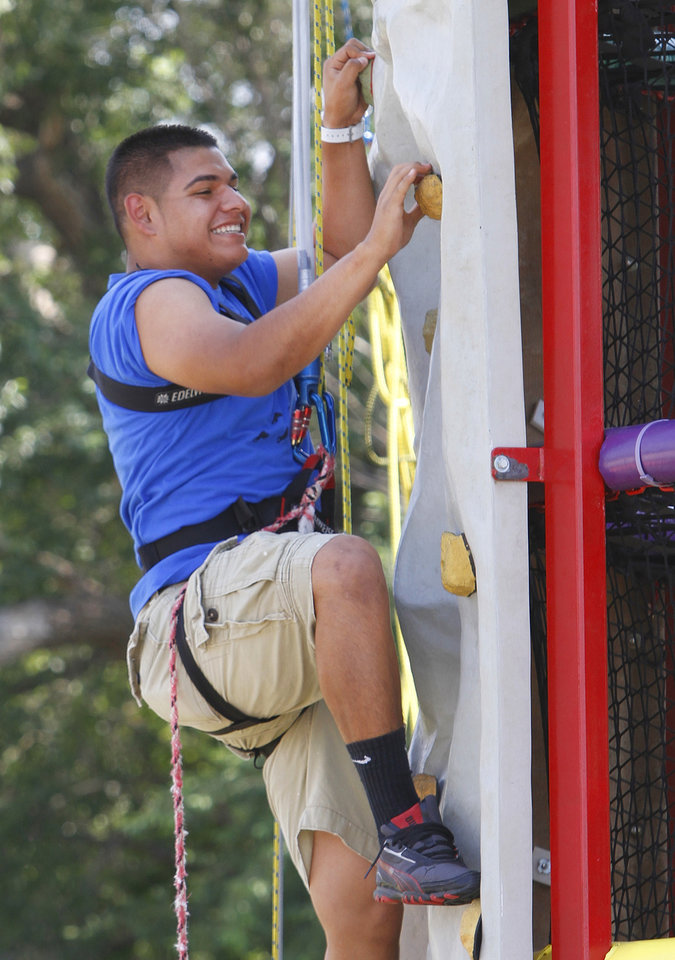 Photo - Gonzalo Vasquez climbs a wall at Faithworks of the Inner City community center in Oklahoma City, Wednesday July 3, 2013. The youth were taking part in a Kanakuk Kampout.  Photo By Steve Gooch, The Oklahoman