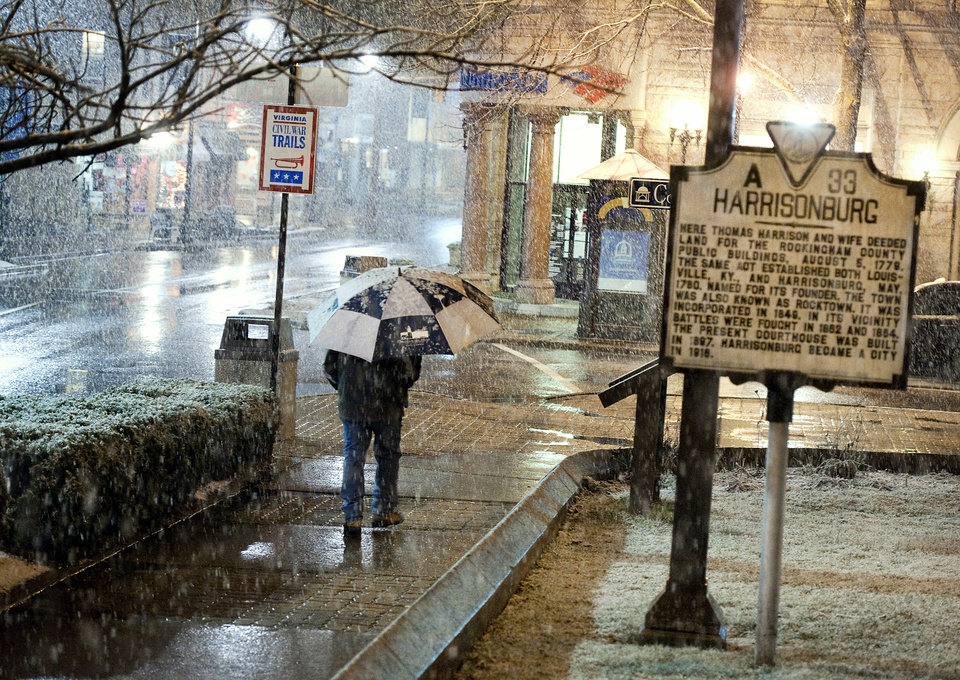 Photo - James Madison University employee John Beach walks to work along Court Square in downtown Harrisonburg, Va., as snow begins to fall Tuesday night, March 5, 2013. (AP Photo/Daily News-Record, Michael Reilly)