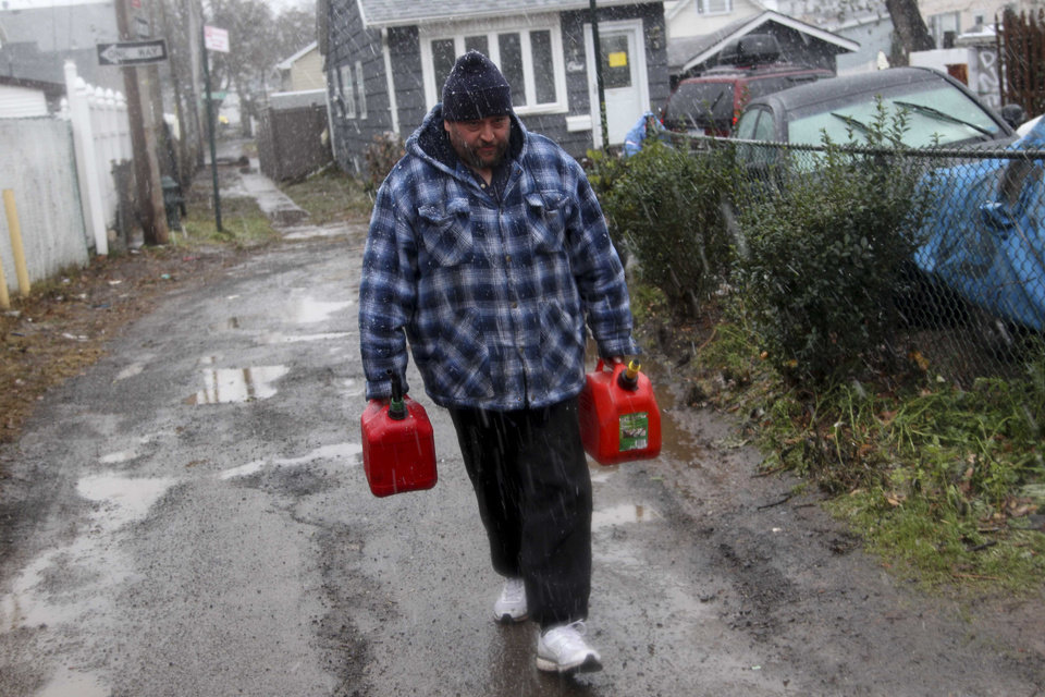 Photo - Joe Graham delivers some gas in the snow to a neighbor for use in her generator in the New Dorp section of Staten Island, N.Y. Wednesday, Nov. 7, 2012.  A nor'easter blustered into New York and New Jersey on Wednesday, threatening to swamp homes all over again, plunge neighborhoods back into darkness and inflict more misery on tens of thousands of people still reeling from Superstorm Sandy.  (AP Photo/Seth Wenig) ORG XMIT: NYSW107
