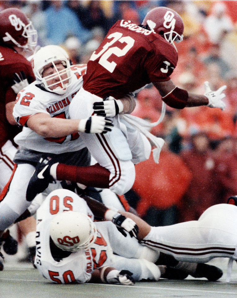 Photo - University of Oklahoma running back Mike Gaddis has the brakes put on by OSU defensive lineman Stacey Satterwhite during the Bedlam college football game on Nov. 16, 1991 in Norman, Okla. OU beat OSU, 21-6.