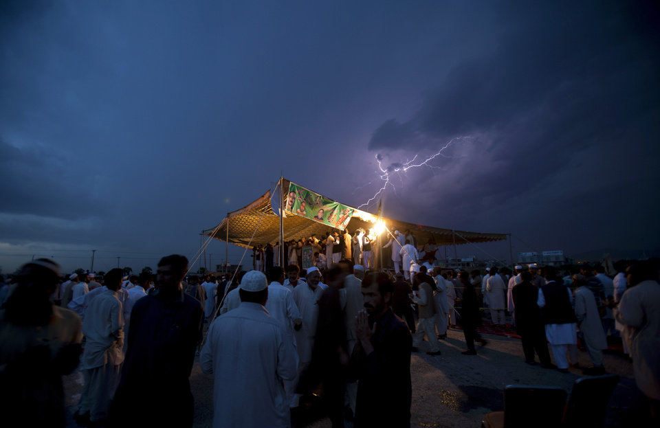 Photo - Lightning flashes as political supporters of the Pakistan Muslim League hold a meeting under tight security due to ongoing attacks on political rallies and parties' election offices, in Islamabad, Pakistan on Friday, April 26, 2013. The Muttahida Qaumi Movement has ordered the closure of election offices in Karachi following a blast that killed many party workers. (AP Photo/B.K. Bangash)